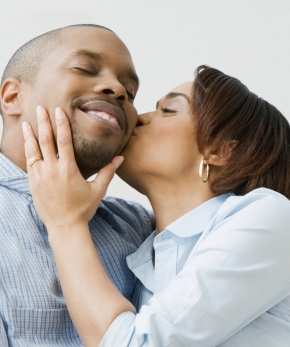 African American man enjoying the affection of his wife