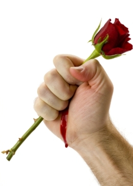 a bleeding hand holding tightly to a beautiful prickly rose